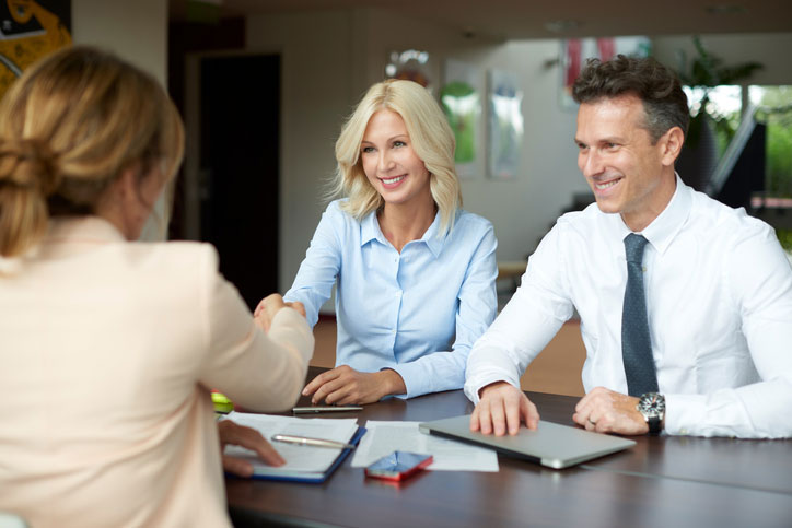 Image of a young couple shaking hands with financial adviser