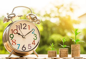 Image of an alarm clock and stack of coins growing roots from the top