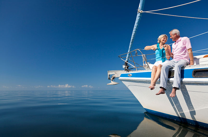 Image of a happy retired husband and wife sitting on a yacht